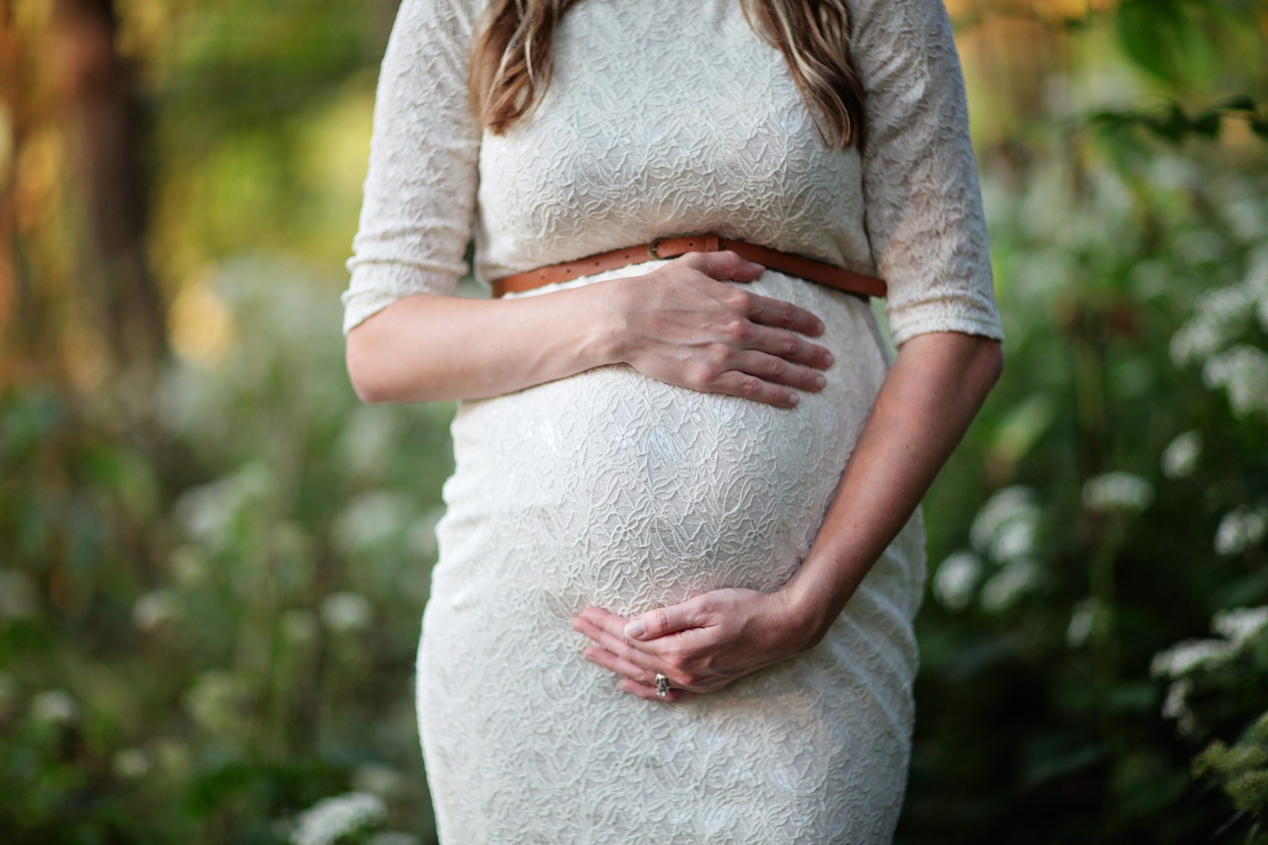 Pregnant woman in white dress holding belly