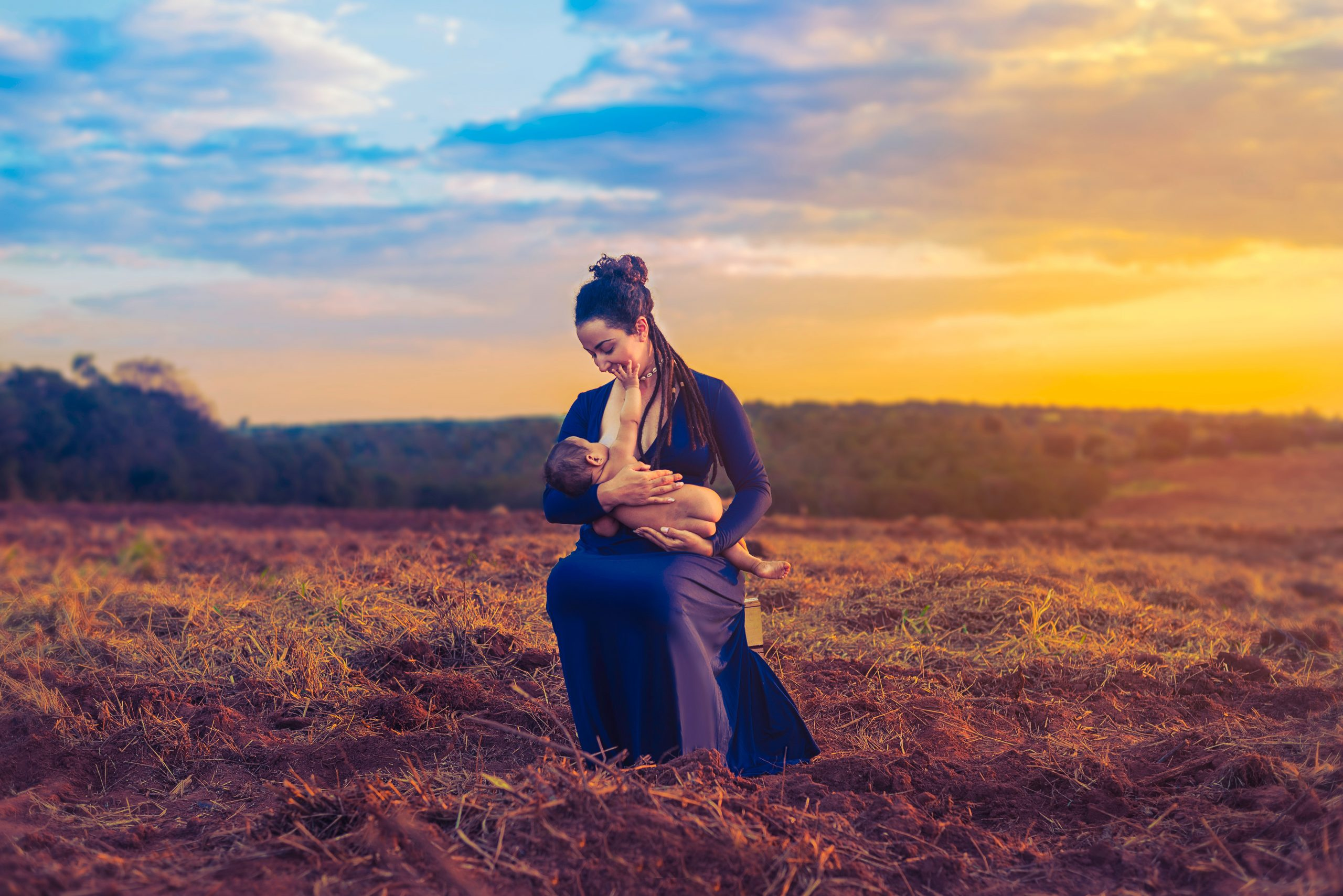 Woman breastfeeding in a field during a sunset