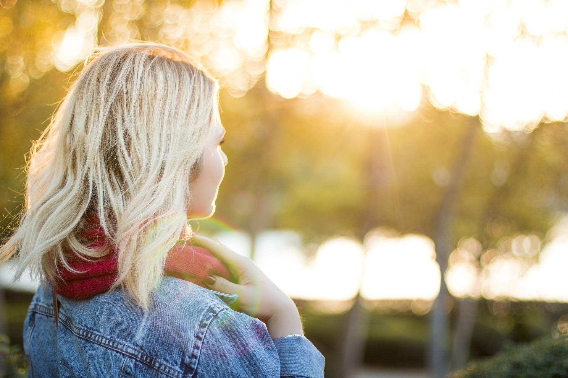 Blonde woman facing sunset outside